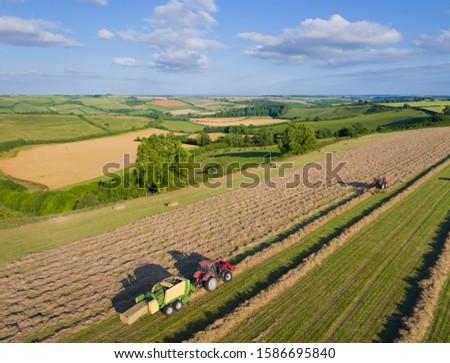 Aerial View Of Tractors Baling Hay In Field #1586695840
