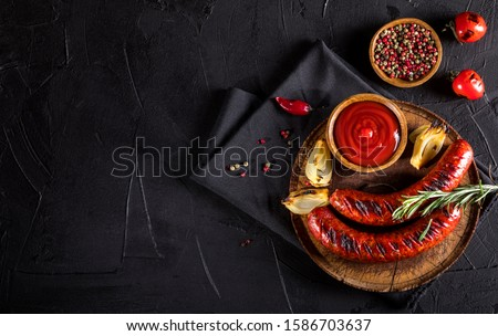 Grilled sausages with spices on black background. Top view with copy space. Royalty-Free Stock Photo #1586703637