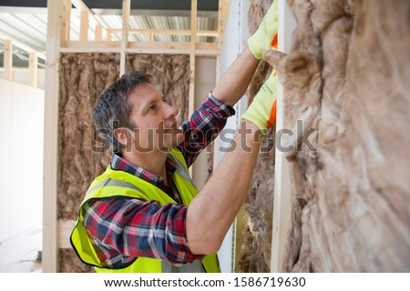 Builder fitting insulation fibre to room walls #1586719630