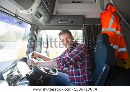 Truck driver in cab of semi-truck #1586719894