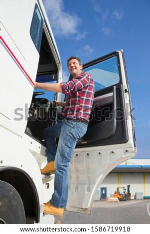 Truck driver climbing into cab of semi-truck #1586719918