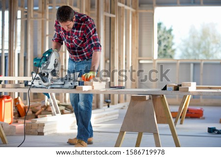 Carpenter using circular power saw to cut wood on indoor building construction site #1586719978