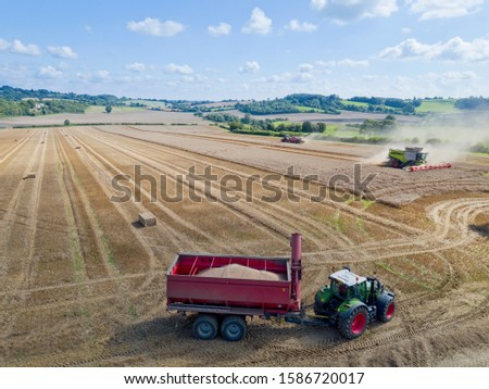 Aerial view of summer country farming landscape and wheat field being harvested by combine harvester with trailer and grain in foreground #1586720017