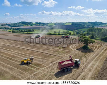 Aerial view of summer country farming landscape and wheat field being harvested by combine harvester with trailer and grain in foreground #1586720026