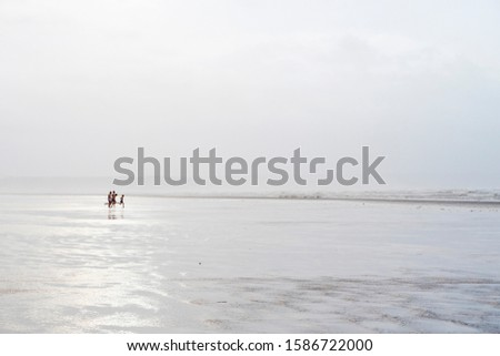 Distant Group Of People Running Along Beach Toward Ocean Royalty-Free Stock Photo #1586722000