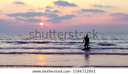 Silhouette Of Male Stand Up Paddle Boarder On Shore At Sunset #1586722861