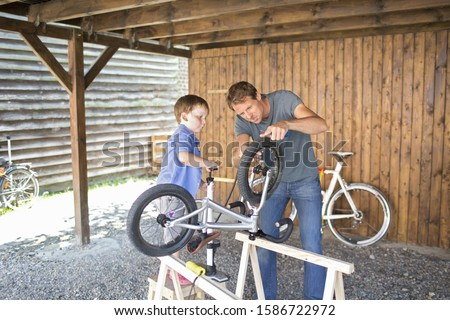 Father And Son Mending Bicycle In Garage At Home #1586722972