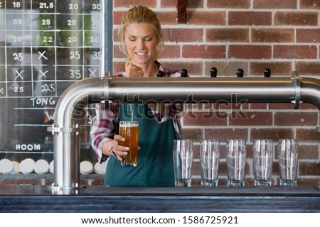 Female Bartender Pouring Pint Of Beer Behind Counter Royalty-Free Stock Photo #1586725921