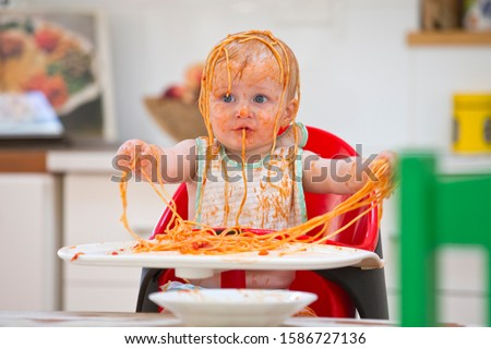 Messy Baby Boy Sits In High Chair Covered In Spaghetti And Sauce #1586727136