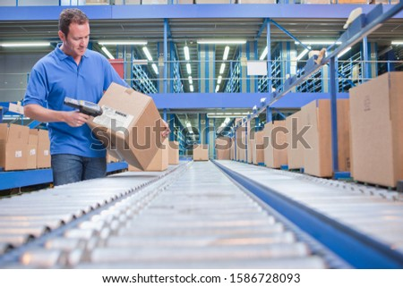Worker Using Scanner In Warehouse Despatch Area #1586728093