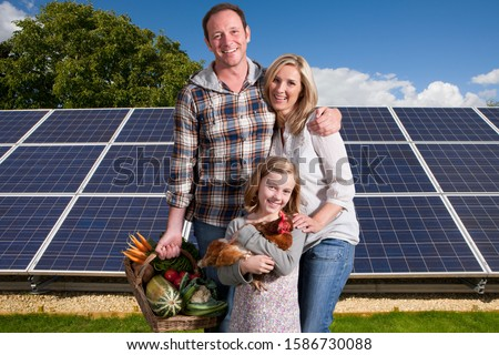 Family With Homegrown Food Standing By Solar Panels #1586730088