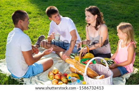 Parents with two teenagers enjoying  delicious meal on the picnic #1586732413