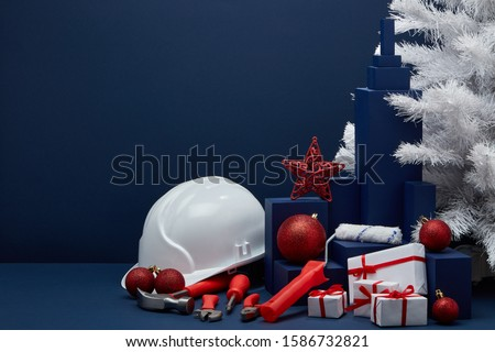 Construction tools, hard hat, white fir tree, gift boxes and Christmas ornaments on dark blue background with copy space. New Year and Christmas construction background. For advertising or web design