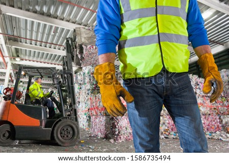 Close Up Of Worker With Forklift Moving Recycling Bales #1586735494
