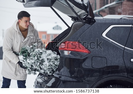 Man in white coat putting christmas fir tree inside his automobile. #1586737138