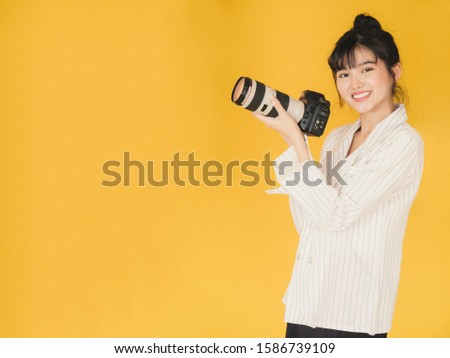 A professional Asian young beautiful Asian female photographer holding a professionally digital camera and looking into the camera, smile and happy on isolated on yellow background. #1586739109