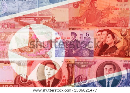 North Korea Won banknotes on national flag background. High resolution vintage photo of North Korean bill, DPRK money close up macro.
