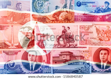 North Korea Won banknotes on waving flag background. High resolution vintage photo of North Korean bill, DPRK money close up macro.