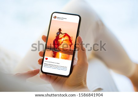 Woman looking at photo on social media app, person names on screen are all made up