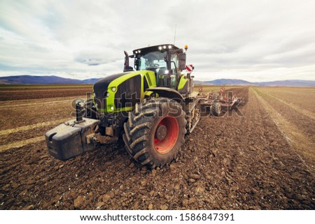 Agriculture. The tractor prepares the ground for sowing and cultivation. Agronomy, the concept of farming. Agricultural machinery for fields, Work of a plow on the field. New modern tractor. #1586847391