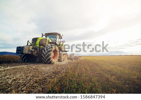 Agriculture. The tractor prepares the ground for sowing and cultivation. Agronomy, the concept of farming. Agricultural machinery for fields, Work of a plow on the field. New modern tractor. #1586847394