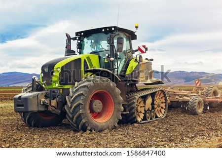 Agriculture. The tractor prepares the ground for sowing and cultivation. Agronomy, the concept of farming. Agricultural machinery for fields, Work of a plow on the field. New modern tractor. #1586847400