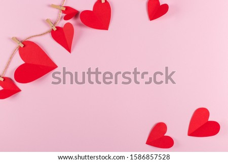 The concept of the preparation for Valentine's Day. Red hearts are held by clothespins on a jute rope, on a pink background. Copy space. #1586857528
