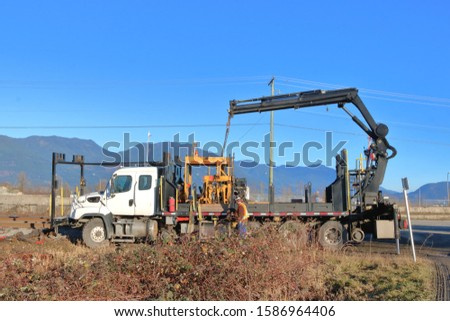 A technician operates a specially equipped vehicle that uses a heavy, industrialized lift to move equipment.  #1586964406