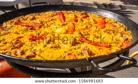 Close up photo of a traditional Paella in Valencia cooking in a typical iron cast big pan on the street during a paella competition in Cullera, Spain. Traditional Spanish street food with rice, veggie #1586981683