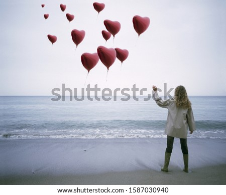View of a woman letting heart-shaped balloons go on the beach #1587030940