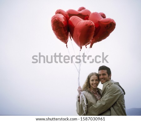 View of a couple hugging and holding heart-shaped balloons #1587030961