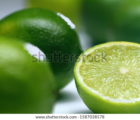 Close-up of limes, one cut in half #1587038578