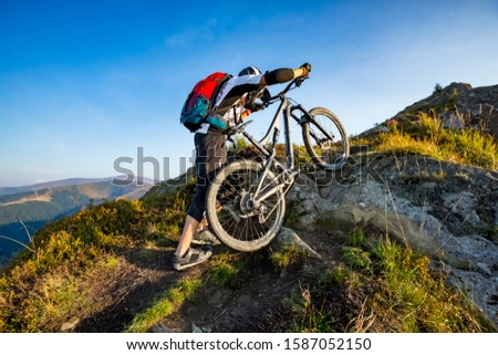 A man is walking up the hill with enduro bicycle, on the rock trail. Background of mountains and blue sky. Beautiful summer day. Mountain bike race. #1587052150