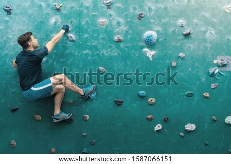A man climbing in boulder gym in the wall. #1587066151