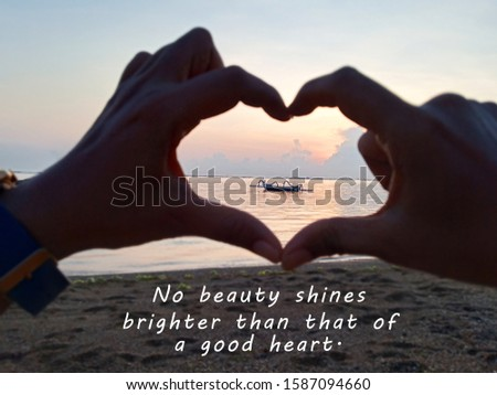 Inspirational quote - No beauty shines brighter than that of a good heart. With blurry hands love sign focus on fishing boat on sea at sunrise. Blurry image of hands love and heart symbol concept.