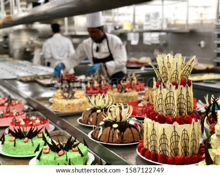 Big selection of cakes on the table. Big galley with many chefs. Cruise ship kitchen, pastry section. #1587122749