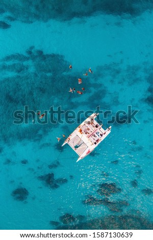 Aerial pic of Sailing boat with peoples on board and swimming outside in the middle of ocean with perfect weather and clean water at sunset time in Hawaii paradise, shot on drone from above