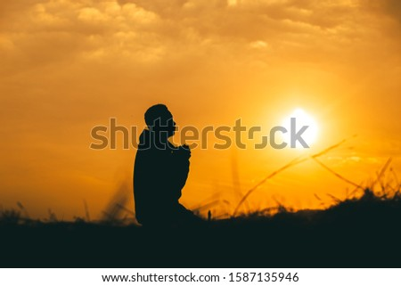 Man kneeling down and praying at sunset background. christian silhouette concept.