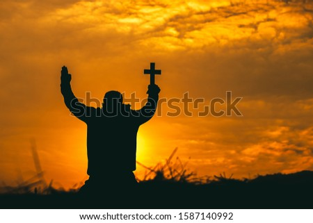 Christian man sitting lift hands and praying to God with christian cross at sunset background. christian silhouette concept.