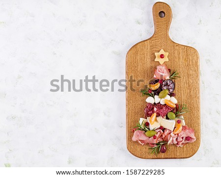Antipasto platter with ham, prosciutto, salami, cheese,  crackers and olives on a light background.  Christmas table. Top view, overhead #1587229285