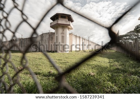 Prison with iron fences.Prison or jail is a building where people are forced to live if their freedom has been taken away.Prison is the building use for punishment prisoner. #1587239341