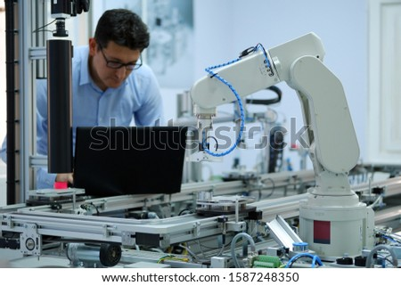 Focus on robotic arm which  picks up product from automated car on production line and an engineer working on laptop at background. Industry 4.0 concept; artificial intelligence in smart factory. #1587248350