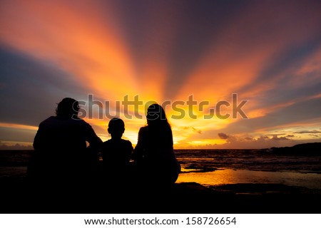 silhouette of family watching sunset at the beach in Phi Phi island