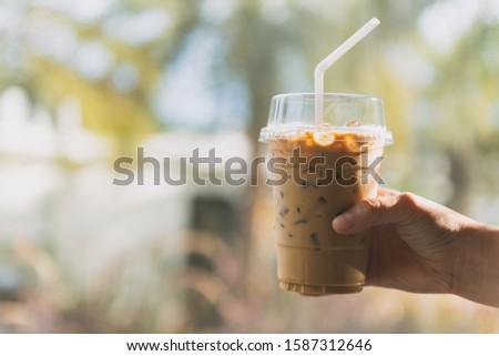 Iced Espresso, Iced Coffee in the hands of a girl At a beverage shop, a coffee shop, vintage style. #1587312646