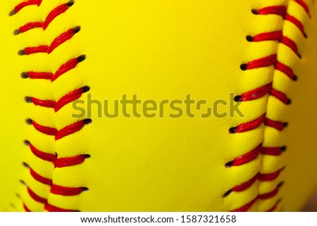 close up of a yellow softball with red stitching.