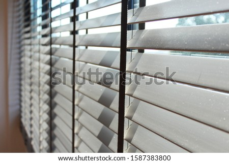 PM2.5 , air pollution crisis make the dust on the Venetian blinds or on the grey wooden blinds. The sun light is shining  through the wooden blinds showing the dust. out. Grey tone with copy space. #1587383800