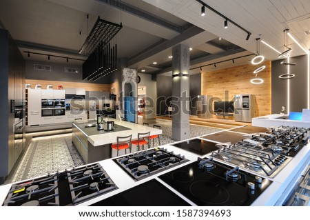 Many gas stoves selling in appliance retail store showroom, ovens and other home appliance at background #1587394693