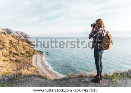Young hip woman with a backpack exploring and photographing the coast on a beautiful day. Concept of exploration and adventures #1587429619