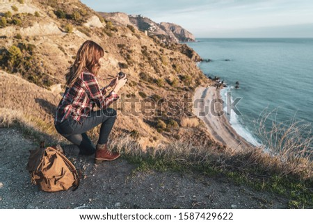 Young hip woman with a backpack exploring and photographing the coast on a beautiful day. Concept of exploration and adventures #1587429622