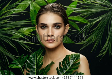 Beautiful woman green palm leaves and evening make-up #1587444175